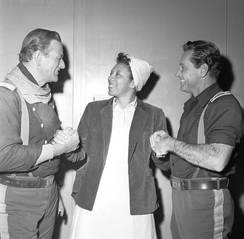 "Description of . Actors John Waynes, left, and William Holden, right, congratulates tennis star Althea Gibson in Los Angeles, Dec. 24, 1958, Gibson is making her movie debut with  upon her selection for the second straight year as female athlete of the year in the annual Associated Press poll. Gibson is making her movie debut with Wayne and Holden in ""Horse Soldiers,\"" under production in Hollywood. (AP Photo/Harold Filan)"
