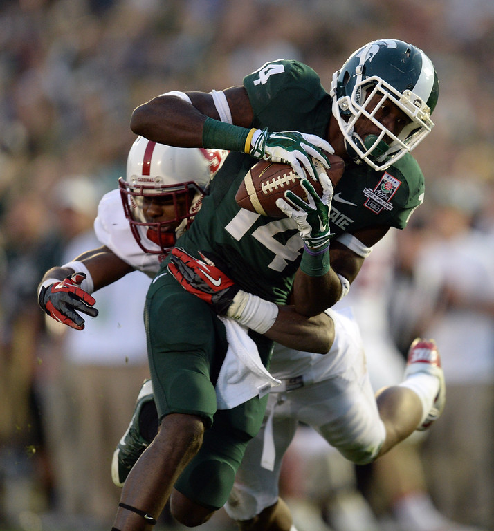 Description of . Michigan State's Tony Lippett #14 escapes the tackle of Stanford's Wayne Lyons #3 to score the go ahead touchdown during the 100th Rose Bowl game in Pasadena Wednesday, January 1, 2014. Michigan State defeated Stanford 24-20. (Photo by Hans Gutknecht/Los Angeles Daily News)