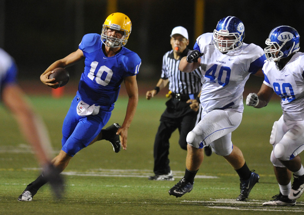 Description of . La Mirada quarterback Kevin Dillman (#10) runs away from La Habra defenders on a keeper play in their football game at La Mirada High School on Friday September 6, 2013. (Whittier Daily News/Staff Photo by Keith Durflinger)