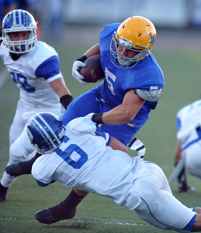 Description of . La Mirada running back Adam Carrasco (#5) carries the ball and is brought down by La Habra's Noah Massman (#6) in their football game at La Mirada High School on Friday September 6, 2013. (Whittier Daily News/Staff Photo by Keith Durflinger)