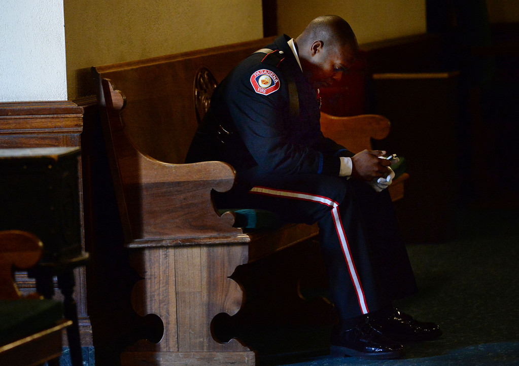 Description of . A member of the pasadena fire dept. takes a moment in the hall way during a celebration of life service for former Pasadena Fire dept. Capt. and California State fire marshall, John Tennant at the Pasadena Civic Auditorium in Pasadena, Calif., on Wednesday, Feb. 5, 2014. (Keith Birmingham Pasadena Star-News)