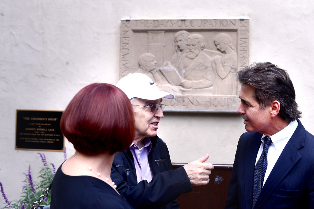 "Description of . South Pasadena Councilman Michael Cacciotti speaks with JIm and Yolanda Giallo, of San Marino, after the unveiling of Merrell Gage's recently restored 1930 bas relief masterpiece, ""The Children's Hour"" at South Pasadena Public Library Friday, March 21, 2014. The 600 lb. stone casting survived fire, breakage, and being buried until it was deemed to possess great local and national significance. (Photo by Sarah Reingewirtz/Pasadena Star-News)"