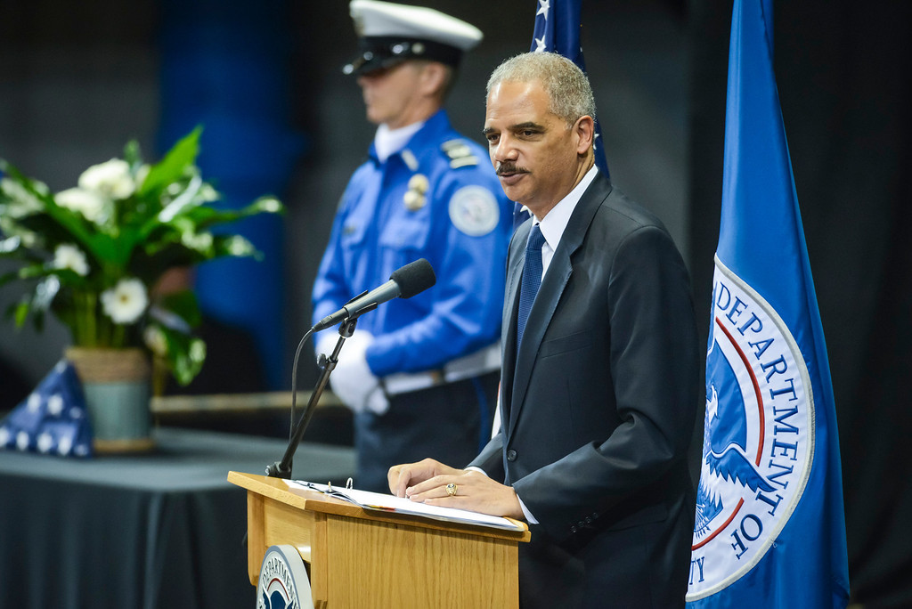 Description of . Attorney General Eric Holder speaks at the memorial for slain TSA officer Gerardo Hernandez at the Los Angeles Sports Arena Tuesday, November 12, 2013.  A public memorial was held for Officer Hernandez who was killed at LAX when a gunman entered terminal 3 and opened fire with a semi-automatic rifle, Grigsby was wounded in the attack.  ( Photo by David Crane/Los Angeles Daily News )