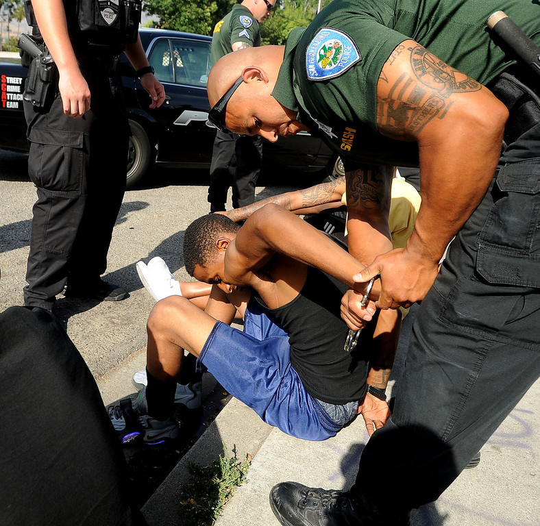 Description of . A young man is detained for questioning outside the Evergreen Apartments along the 1500 block of Pumalo Street during a county wide police sweep in San Bernardino August 2, 2013. GABRIEL LUIS ACOSTA/STAFF PHOTOGRAPHER.