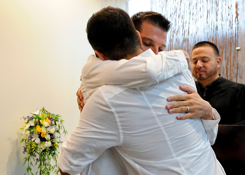 Description of . Christopher Persky, 32, left, and his partner of 10 years Ken Bencomo, 45, both of Rancho Cucamonga, tearfully embrace after getting married at the San Bernardino County Hall of Records in San Bernardino on Monday, July 1, 2013. (Rachel Luna / Staff Photographer)