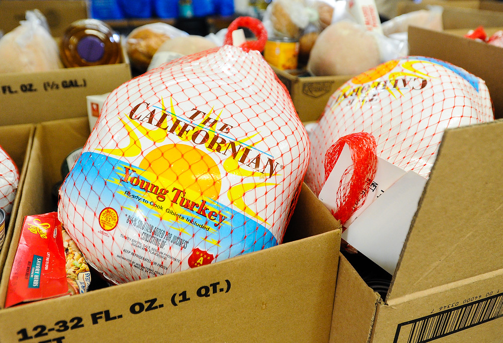 Description of . Free Thanksgiving dinner baskets are packed and wait to be distributed at 16th Street Seventh-day Adventist Church in San Bernardino on Tuesday, Nov. 26, 2013. The church gave 175 baskets to families-in-need. (Photo by Rachel Luna / San Bernardino Sun)