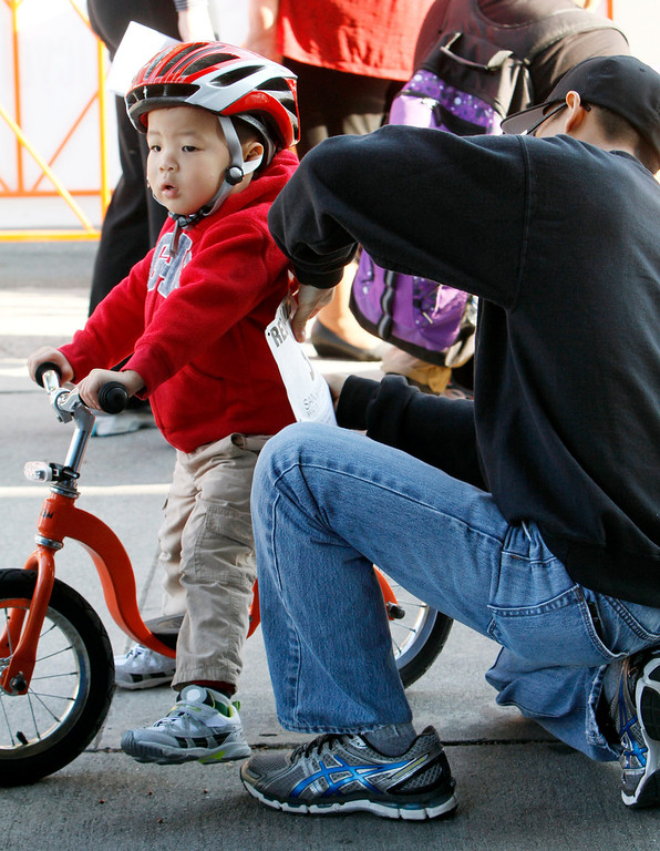 Description of . Brandon Gabot, 3, left, gets his bib pinned on by his father Mark prior to the start of the public race portion of the Redlands Bicycle Classic on Saturday, April 5, 2014 in Redlands, Ca. (Photo by Micah Escamilla for the Redlands Daily Facts)