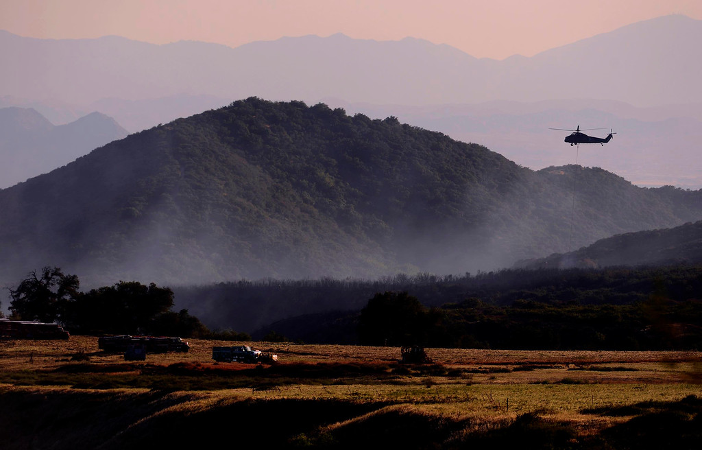 Description of . A helicopter prepares a drop in Mias Canyon as firefighters continue to fight the Summit Fire in Banning May 2, 2013.   GABRIEL LUIS ACOSTA/STAFF PHOTOGRAPHER.