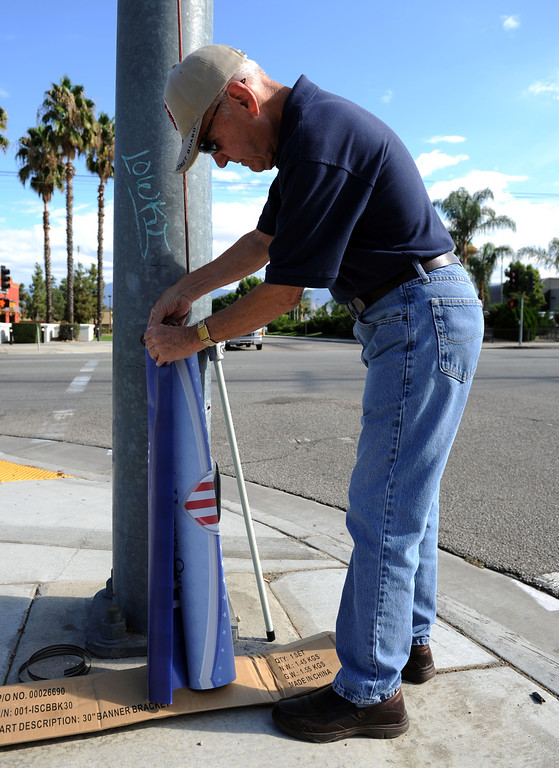 Description of . (John Valenzuela/Staff Photographer) Redlands Evening Kiwanis Club member Gary Cross get ready to send up a Hometown Heroes banner of Redlands' Naval officer Samantha Kelly at the corner of New Jersey St. and Redlands Blvd., Tuesday, August 27, 2013. Kelly is a 2006 Redlands East Valley grad.
