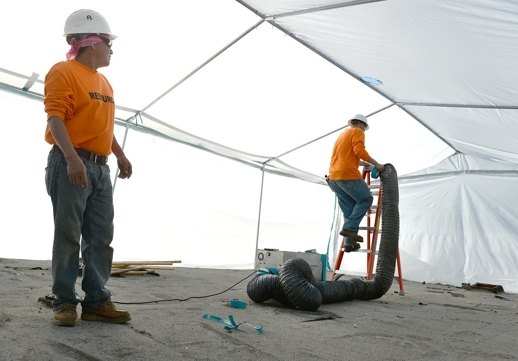 Description of . Resource Environmental, Inc. workers set up an isolation tent as they remove Asbestos from La Habra Heights City Hall on Wednesday January 22, 2014. More asbestos was found in the roofing material last week. (Staff Photo by Keith Durflinger/Pasadena Star-News)