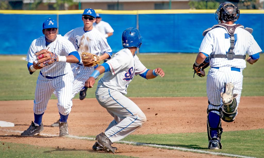 Description of . Serra High's Morgan Lomax, center, evades a Bishop Amat third inning rundown to score at Amat's La Puente, Calif. campus field April 16, 2014.  (Staff photo by Leo Jarzomb/San Gabriel Valley Tribune)