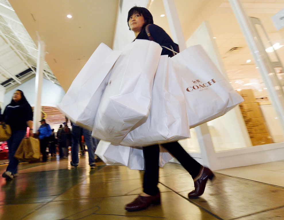 Description of . A shopper leaves a store with an arm load of bags after making a purchase Thursday night November 28, 2013 at the Ontario Mills. Thousands of holiday shoppers descend on the Ontario Mills Thursday night November 28, 2013 for the malls 8p.m. opening. (Will Lester/Inland Valley Daily Bulletin)