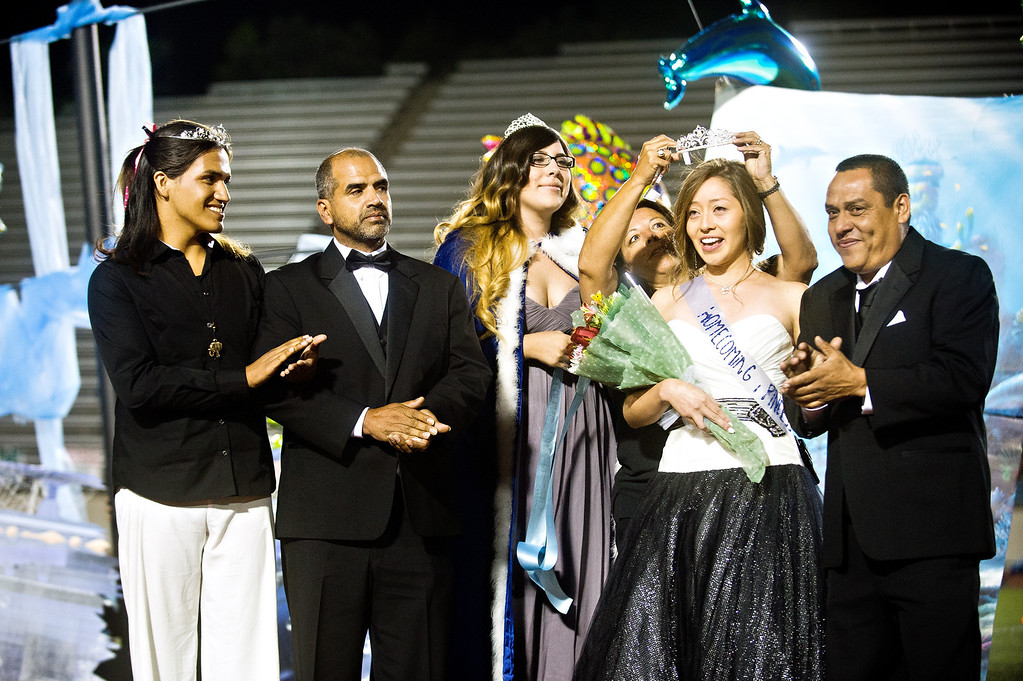 Description of . Patrick Cordova, 16, a transgender senior, left, applauses with dad, Jose Cordova, after Ivory Gomez Gonzalez is crown Azusa High 2013 Homecoming Queen during halftime of the homecoming football game at Citrus College Stadium in Glendora on Friday night, Sept. 27, 2013. (Photo by Watchara Phomicinda/ San Gabriel Valley Tribune)