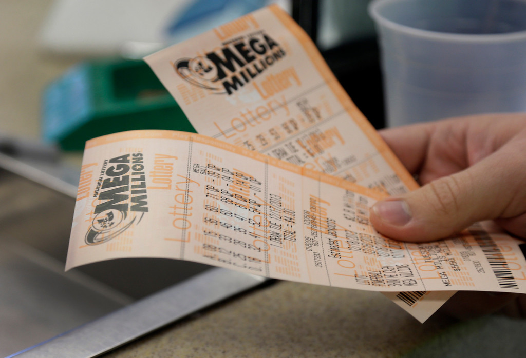 Description of . Scott Hoormann holds two Mega Millions lottery tickets he purchased at Energy Express Monday, Dec. 16, 2013, in St. Louis. The Mega Millions jackpot now stands at an estimated $586 million with the next drawing set for Tuesday night. (AP Photo/Jeff Roberson)