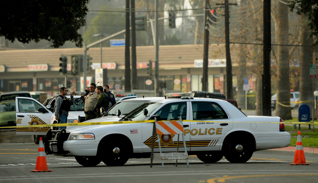Description of . San Bernardino County Sheriff officers take a positionat at the intersection of Arlington and Magnolia Avenues in Riverside where fugitive Christopher Dorner shot two Riverside officers killing one in Riverside February 7, 2012.  Arrests warrants for Christopher Dorner  have been released to the public by the County of Riverside. (Photo by Gabriel Luis Acosta/The Sun)