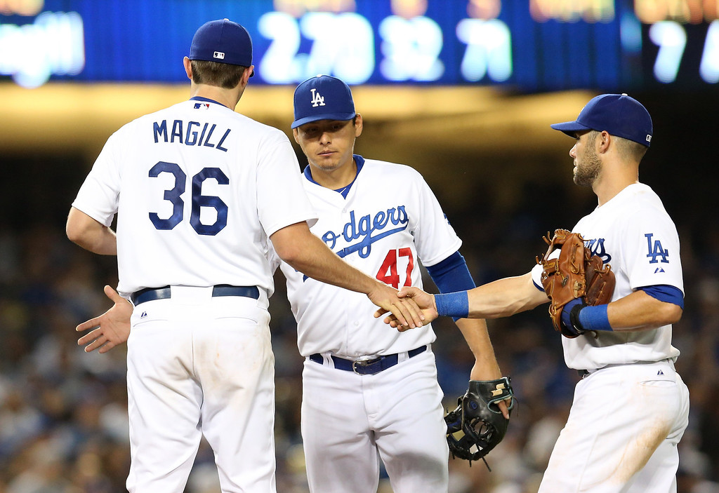 Description of . Matt Magill #36 of the Los Angeles Dodgers is congratulated by Luis Cruz #47 and Skip Schumaker #3 as Magill is relieved in the seventh inning after his first Major League start and appearance, against the Milwaukee Brewers at Dodger Stadium on April 27, 2013 in Los Angeles, California.  (Photo by Stephen Dunn/Getty Images)