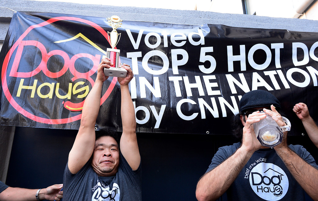 Description of . Jimmy Lin, of Anaheim, wins the First Annual Hot Dog Eating Competition at Dog Haus Biergarten in Old Pasadena Saturday, July 6, 2013 while next to the third place winner Naader Reda, of Victorville. Lin ate 11 dogs, 3 during a tiebreaker.  (SGVN/Staff Photo by Sarah Reingewirtz)