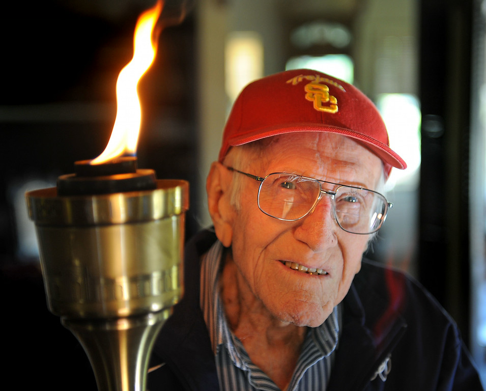 Description of . Louis Zamperini, 94, at his Hollywood home holds the Olympic torch he carried at the 1984 Olympic Games. Zamperini died on July 2, 2014,  He was 97.  http://bit.ly/1pIbk1O   (Photo by Brad Graverson/Daily Breeze) 11-7-10