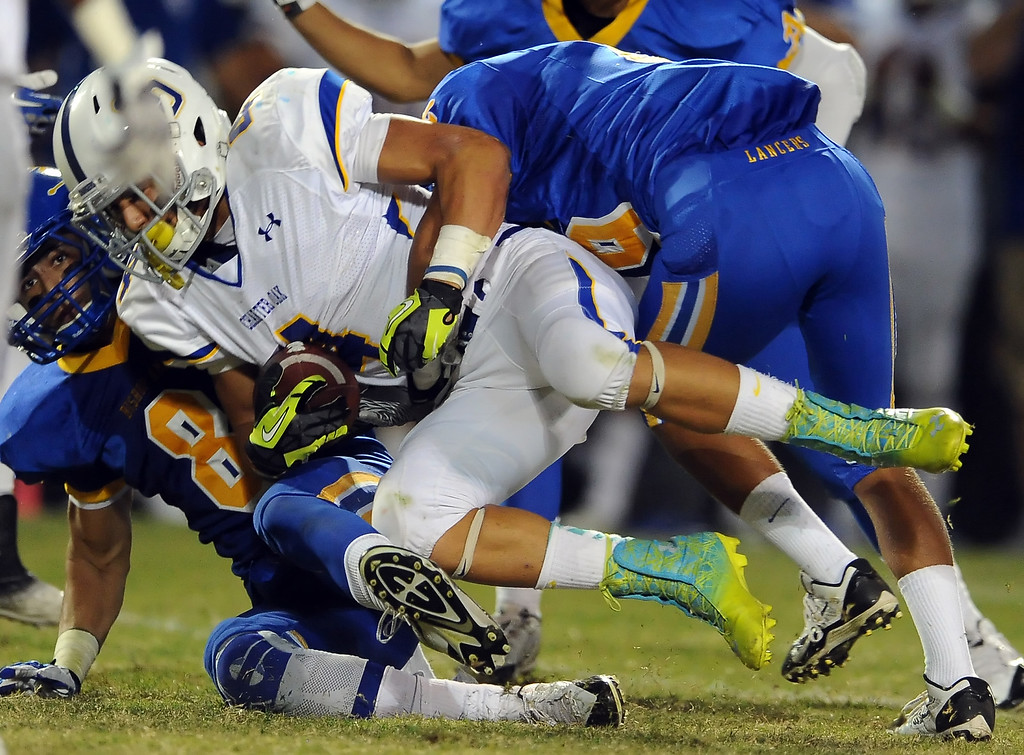 Description of . Bishop Amat defense tackles Charter Oak's Donavin Washington (4) in the first half of a prep football game at Bishop Amat High School in La Puente, Calif. on Friday, Sept. 20, 2013.    (Photo by Keith Birmingham/Pasadena Star-News)