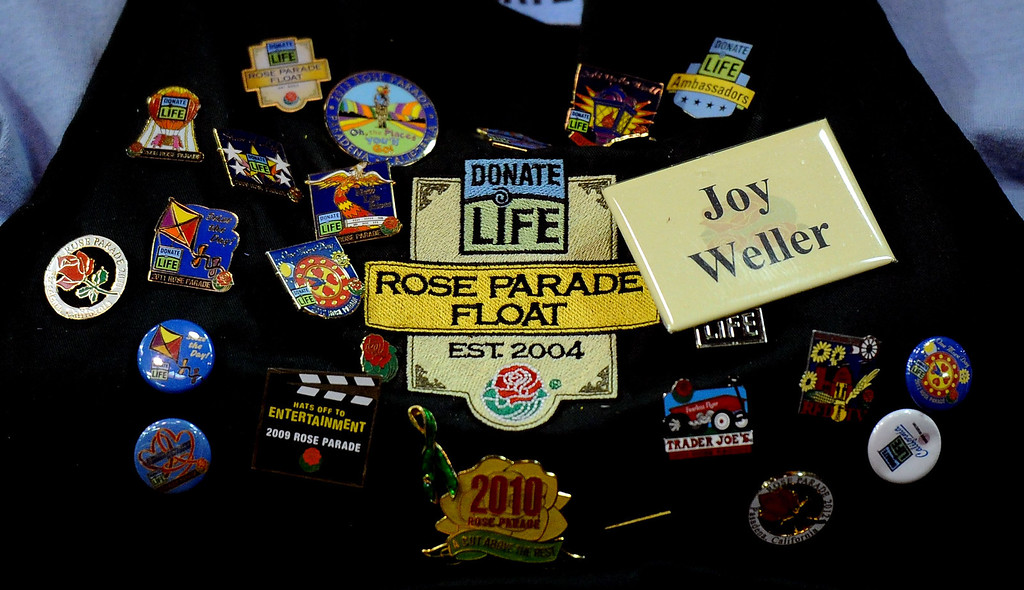 Description of . Joy Weller shows-off her pin collection during the final stages of preparation for the 2014 Rose Parade as a variety of seeds, bark, fruits and vegetables, grasses and of course, flowers are being applied to the floats by experienced professionals as well as hard working volunteers at the Rosemont Pavilion in Pasadena, Calif., on Saturday, Dec. 28, 2013.     (Keith Birmingham Pasadena Star-News)
