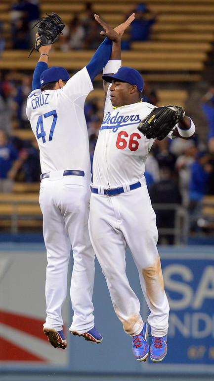 Description of . New Dodger Yasiel Puig celebrates with Luis Cruz after Puig completed a double play to end the game against the Padres June 3, 2013 in Los Angeles, CA.  The Dodgers won the game 2-1. (Andy Holzman/Los Angeles Daily News)