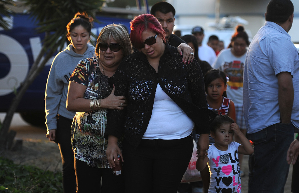 Description of . Myra Velasquez, center, wife of Efren Velasquez is consoled by friends and family as she makes her way to a make shift memorial for those who died in a car crash including two children and a man along the 3500 block of San Gabriel River Road on Friday, June 14, 2013 in Industry, Calif.  (Keith Birmingham/Pasadena Star-News)