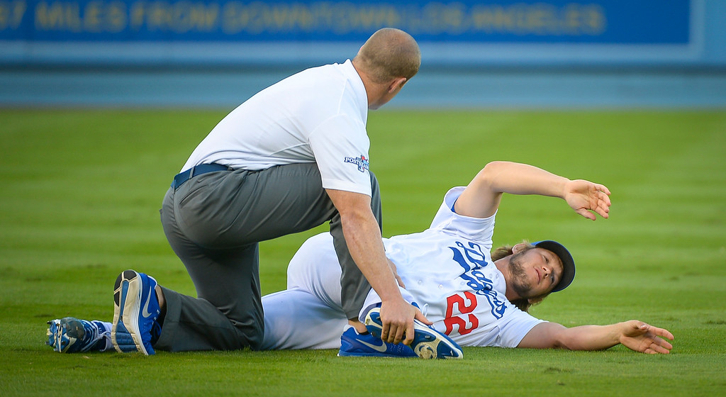 Description of . Dodgers' Clayton Kershaw gets stretched before game 4 against Atlanta Monday, October 7, 2013 ( Photo by Andy Holzman/Los Angeles Daily News )