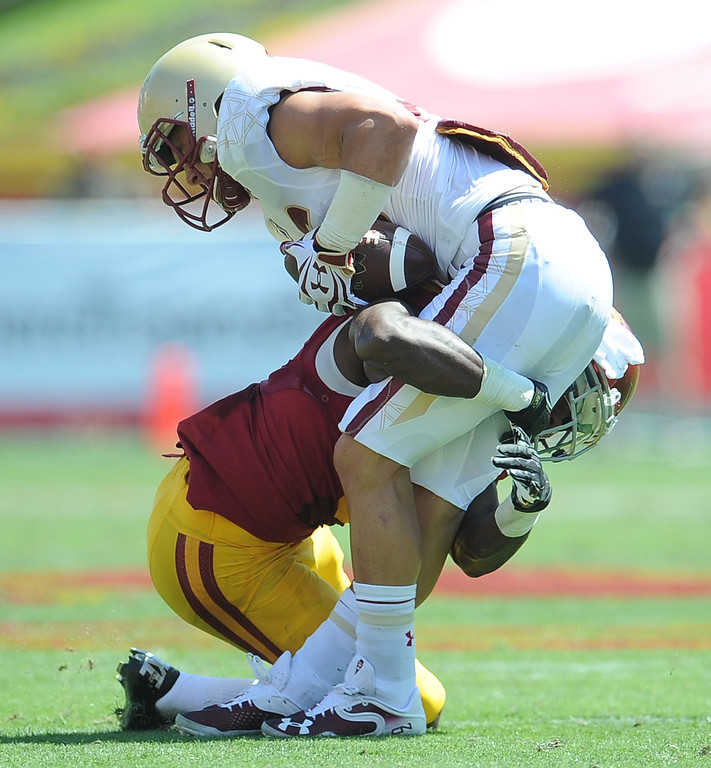 Description of . Southern California's Josh Swah, let, tackles Boston College running back David Dudeck for a loss of yards during the first half of an NCAA college football game in the Los Angeles Memorial Coliseum in Los Angeles, on Saturday, Sept. 14, 2013.