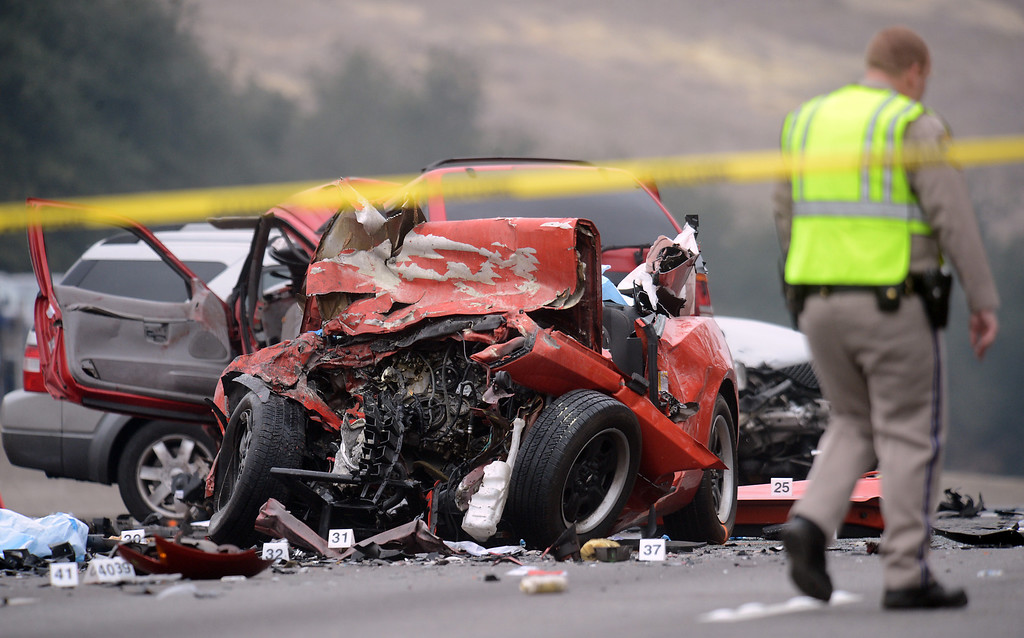 Description of . CHP investigates the scene of a fatal traffic collision, where six people were killed, involving a wrong way driver on the westbound 60 freeway in Diamond Bar, CA., Sunday, February 9, 2014. (Photo by Jennifer Cappuccio Maher/Inland Valley Daily Bulletin)