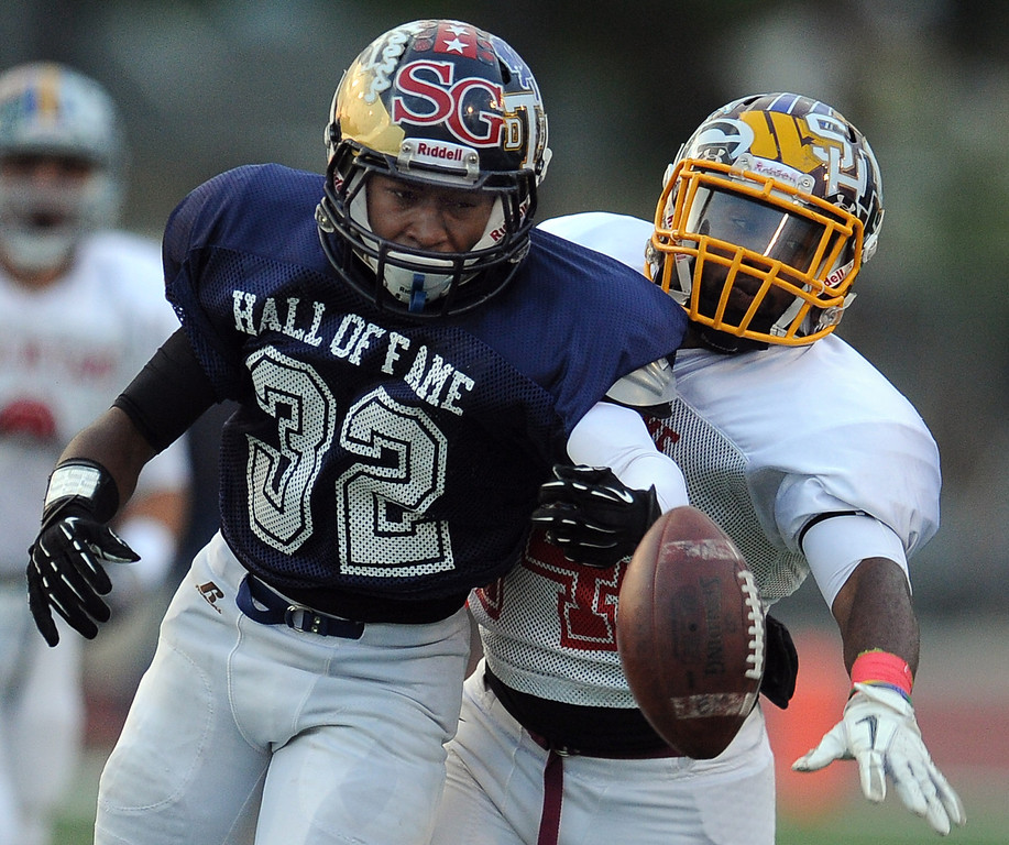 Description of . West's Ezra Broadus (32) (Alhambra) reaches for a pass as he his defended by East's Aaron Franklin (44) (West Covina) in the first half of the annual East vs. West San Gabriel Valley Hall of Fame all-star football game at West Covina High School on Friday, May 17, 2013 in West Covina, Calif.  (Keith Birmingham Pasadena Star-News)