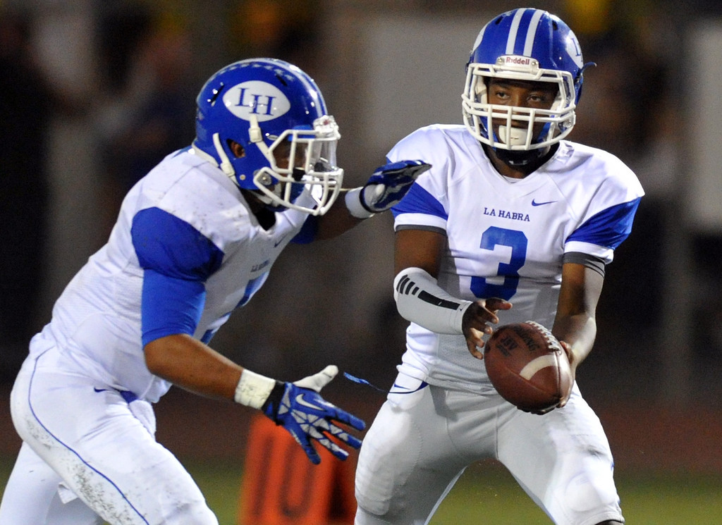 Description of . La Habra quarterback Eric Barriere, Jr. (#3) hands the ball off to running back Carlos Martin (#5) as they play La Mirada in their football game at La Mirada High School on Friday September 6, 2013. (Whittier Daily News/Staff Photo by Keith Durflinger)