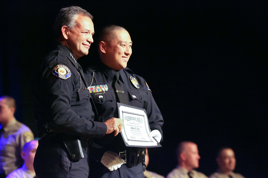 Description of . Rio Hondo Police Academy graduate John Yoo, posses with Pasadena Police Chief Phillip Sanchez for family photos. This is the first class to graduate from the Academy since shutting down in 2010. The graduation took place Saturday July 13, 2013 at the Rio Hondo College Wray Theatre. (Correspondent photo by Chris Burt)