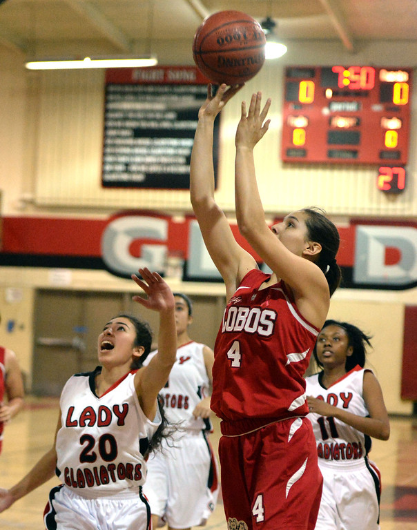 Description of . Workman's Raquel Ramirez (4) drives to the basket past Gladstone's Jessica Rosas (C) (20) in the first half of a prep basketball game at Gladstone High School in Covina, Calif., on Friday, Jan. 17, 2014. (Keith Birmingham Pasadena Star-News)