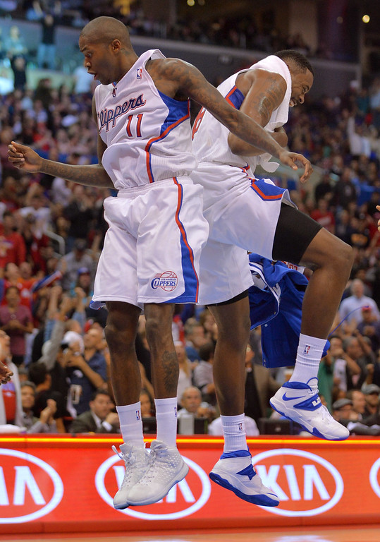 Description of . Los Angeles Clippers' DeAndre Jordan celebrates with Jamal Crawford after Crawford sank a half court shot to end the 3rd quarter against the Minnesota Timberwolves Monday, Nov. 11, 2013, in Los Angeles.  The Clippers won the game 109-107.(Andy Holzman/Los Angeles Daily News)