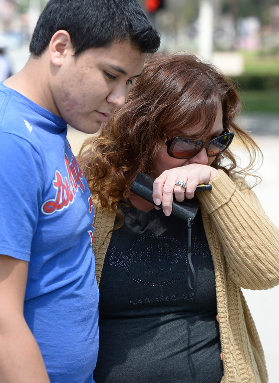 Description of . Andrew and his mother Ruth Escalera are emotional as they look at the memorial. Andrew graduated last year from the rival high school, South El Monte H.S. Students at El Monte High School brought flowers, candles and other items in remembering Adrian Castro, a Senior student who was killed in bus crash in Northern California that took the lives of 10 people.El Monte, CA. 4/13/2014(Photo by John McCoy / Los Angeles Daily News)