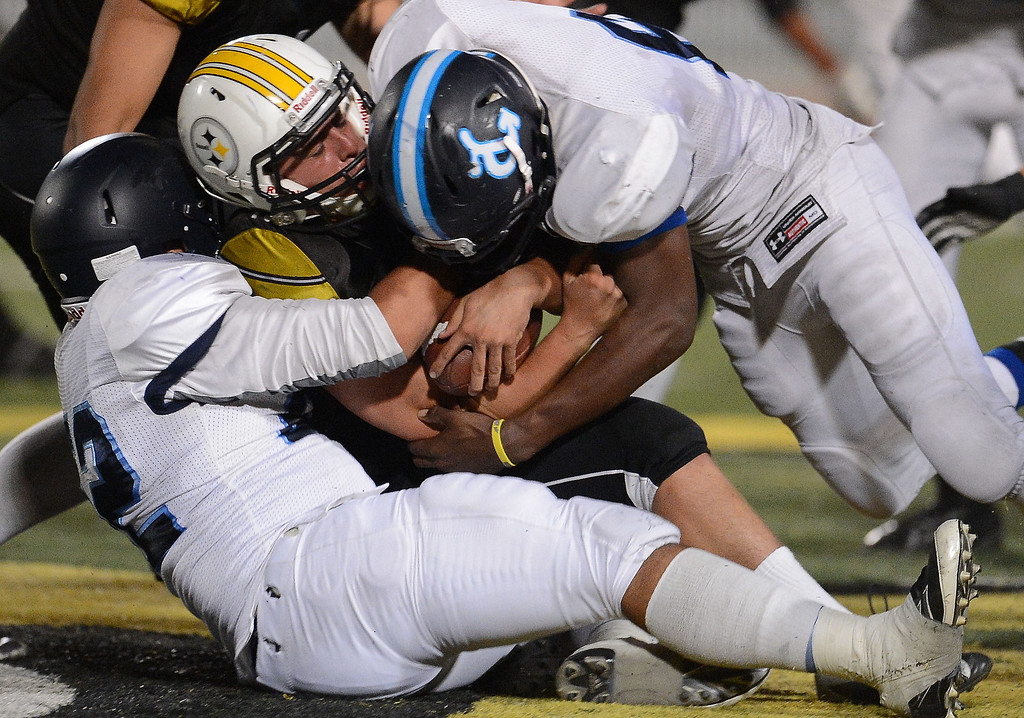 Description of . Duarte defense tackles Bassett quarterback Nicolas Colmenero (10) for a loss of of yards in the first half of a prep football game at Bassett High School in La Puente, Calif., on Friday, Nov. 1, 2013.    (Keith Birmingham Pasadena Star-News)