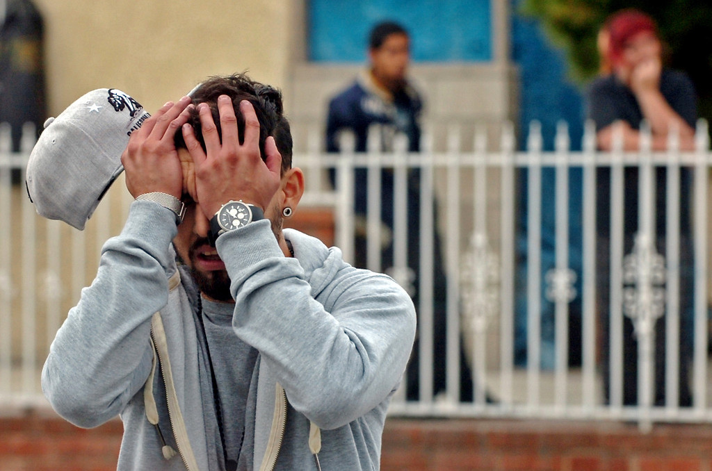 Description of . A man reacts after seeing his cousin, Kelly Buruan, 24 who was shot and killed in a drive by shooting on West 9th Street near Hamilton Blvd in Pomona March 7, 2013. The shooter is still at large. This was the 4th of a string of deadly shootings that have hit the city that has left 23 dead of gun violence as of October 23, 2013. The shooter is still at large. (Staff photo by Thomas Cordova)