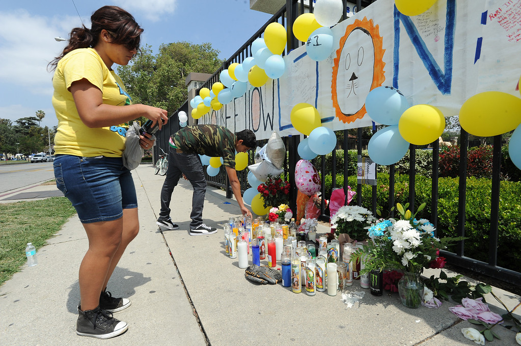 Description of . Jasmine Revelos,17, and Jorge Padilla,17, pay respects at the memorial of their classmate. Students at El Monte High School brought flowers, candles and other items in remembering Adrian Castro, a Senior student who was killed in bus crash in Northern California that took the lives of 10 people. El Monte, CA. 4/13/2014(Photo by John McCoy / Los Angeles Daily News)