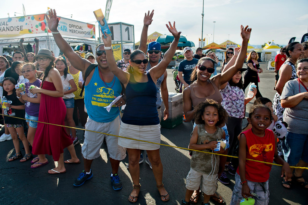 Description of . Crowds wave at the fair parade during opening day of L.A. County Fair in Pomona on Friday, Aug. 30, 2013. (Staff photo by Watchara Phomicinda/ San Gabriel Valley Tribune)