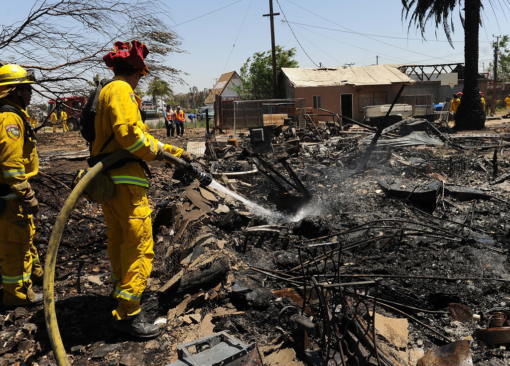 Description of . A vegetation fire in Jurupa Valley is 100 percent contained after destroying two homes and damaging two others.