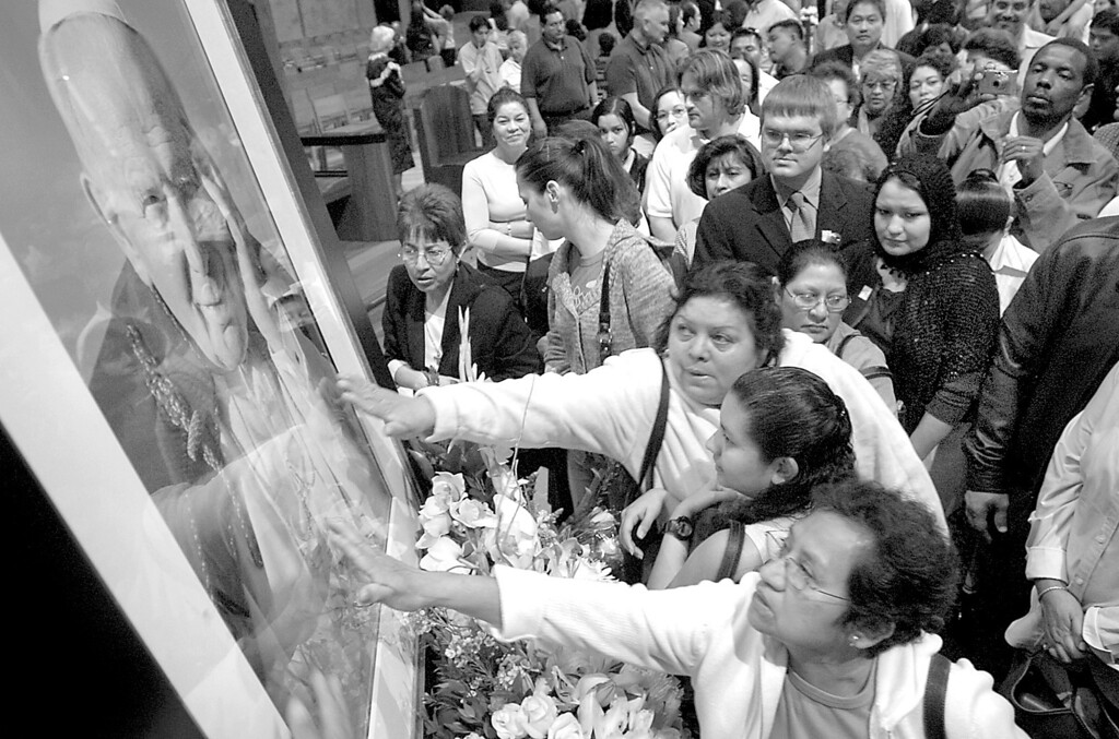 Description of . 4/2/05--LOS ANGELES-- Parishioners crush together to touch a portrait of the deceased Pope John Paul II following Saturday's mass at Cathedral of Our lady of the Angels in downtown Los Angeles.   (Michael Owen Baker/Los Angeles Daily News)