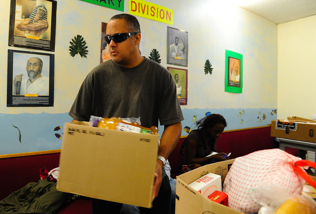 Description of . Church volunteer Dorian Verne help hand out free Thanksgiving dinner baskets at 16th Street Seventh-day Adventist Church in San Bernardino on Tuesday, Nov. 26, 2013. The church distributed 175 baskets to families-in-need. (Photo by Rachel Luna / San Bernardino Sun)