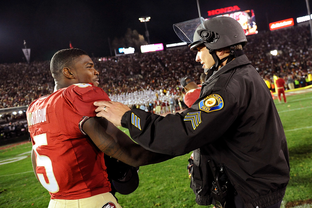 Description of . Florida State's Reggie Northrup is congratulated by a Pasadena police officer following the 2014 Vizio BCS National Championship January 6, 2014 in Pasadena CA.  Florida State won the game 34-31.(Andy Holzman/Los Angeles Daily News)
