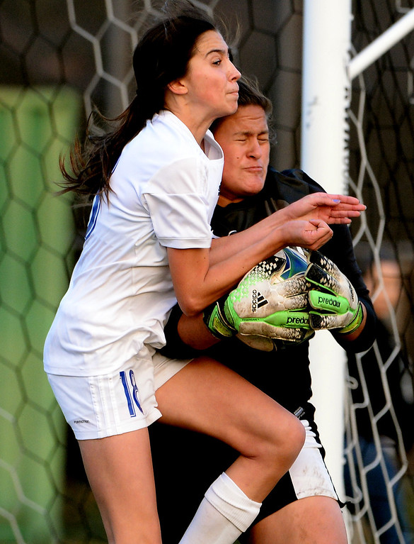 Description of . Bishop Amat's Ashley Rushlow (18) goes-up for the ball with Marshall goal keeper Ariel Martinez (1) in the second half of a prep soccer match at Bishop Amat High School in La Puente, Calif., on Thursday, Jan. 9, 2014.Amat won 3-0. (Keith Birmingham Pasadena Star-News)
