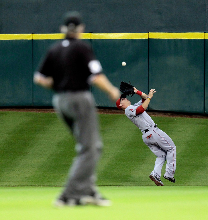 Description of . HOUSTON, TX - SEPTEMBER 14:  Mike Trout #27 of the Los Angeles Angels of Anaheim makes a catch in center field on a fly ball against the Houston Astros at Minute Maid Park on September 14, 2013 in Houston, Texas.  (Photo by Bob Levey/Getty Images)