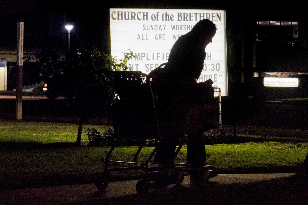 Description of . With her belongings, a homeless women walks in the dark after receiving meals from Nurses4Christ outside Church of the Brethren in Glendora on Wednesday night, Nov. 27, 2013. For the past seven years Nurses4Christ, a nonprofit organization, have been feeding homeless people sandwiches and hot food throughout Glendora and nearby cities. (Photo by Watchara Phomicinda/San Gabriel Valley Tribune)