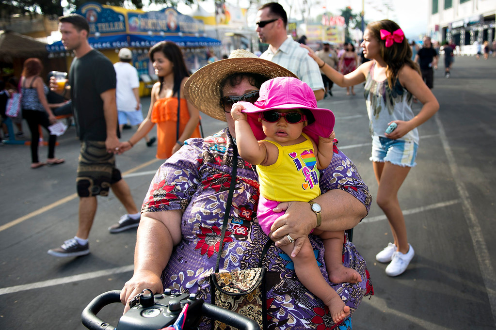 Description of . Judy Rocha, of Wilmington, holds her 8-month-old granddaughter, Bonni Georgeanne as they cruise the opening day of L.A. County Fair in Pomona on Friday, Aug. 30, 2013. (Staff photo by Watchara Phomicinda/ San Gabriel Valley Tribune)