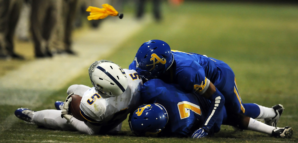 Description of . Bishop Amat defense tackles Charter Oak's Todd Greene (5) as a flag is tossed in the first half of a prep football game at Bishop Amat High School in La Puente, Calif. on Friday, Sept. 20, 2013.    (Photo by Keith Birmingham/Pasadena Star-News)