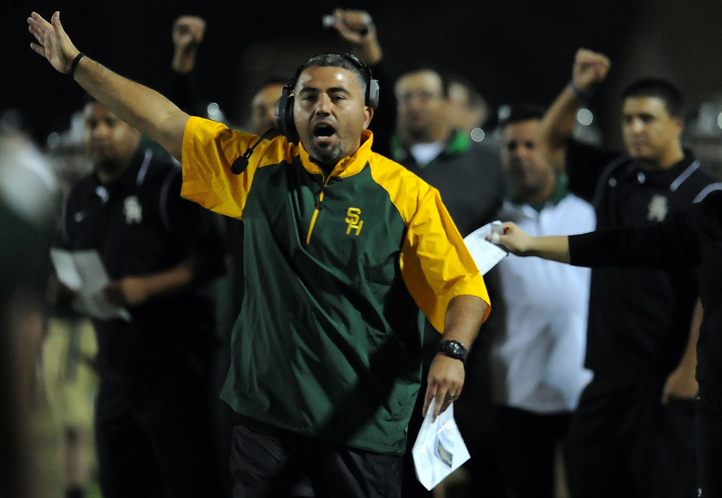 Description of . South Hills head coach Albert Rodriguez reacts after a fumble recovery against Charter Oak in the first half of a prep football game at Covina DIstrict Field in Covina, Calif., on Thursday, Oct. 24, 2013. 
