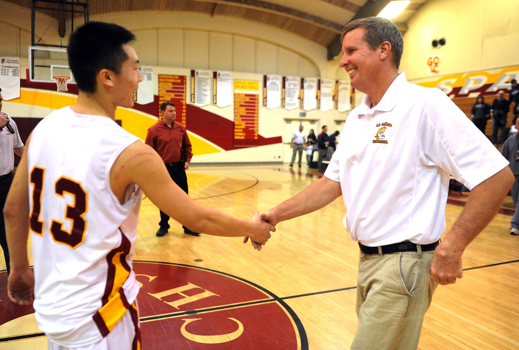 Description of . La Canada head coach Tom Hofman shakes hands with Dan Jun (13) after winning his 600th game as they defeated La Salle 73-62 during a prep basketball game at La Canada High School in La Canada, Calif., on Friday, Jan. 10, 2014. Hofman record is 600 wins and 186 losses since becoming varsity head coach in the 1986-87 season. (Keith Birmingham Pasadena Star-News)